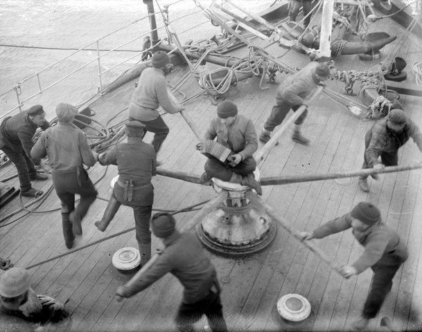 A crew on a ship spinning a wheel together